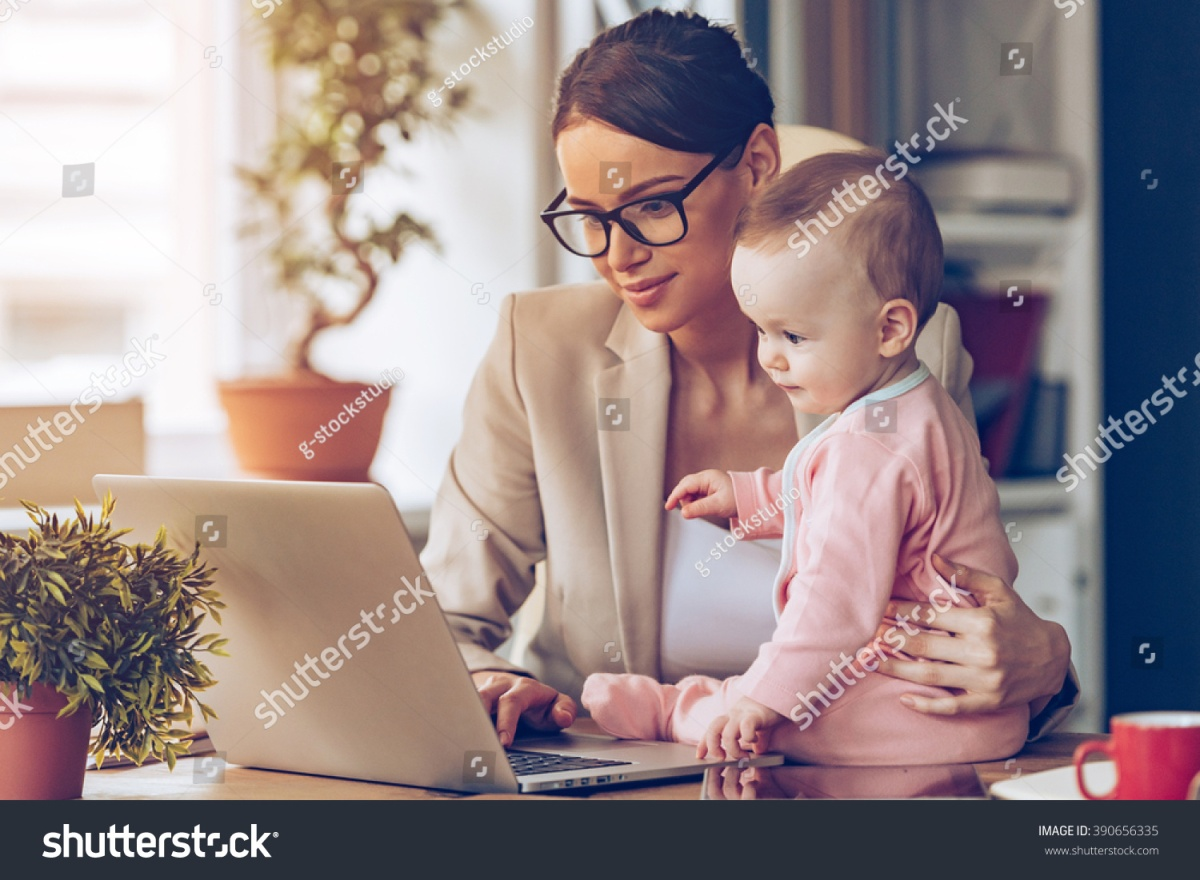 stock-photo-working-together-young-beautiful-businesswoman-using-laptop-while-sitting-with-her-baby-girl-at-390656335-1.jpg